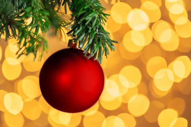 Bola vermelha de natal pendurado no galho de árvore do abeto sobre luzes douradas bokeh