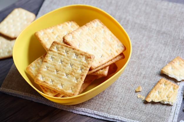 Bolacha com sal na tigela amarela na mesa de madeira e saco