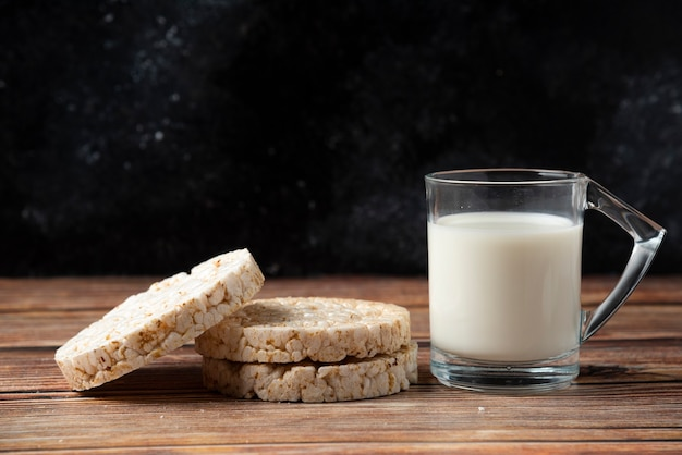 Bolacha de arroz e copo de leite na mesa de madeira.