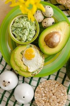 Bolacha de trigo sarraceno com requeijão, espinafre, abacate e ovo de codorna frito