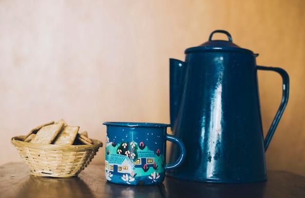 Bolachas caseiras crocantes finas caseiras; bule de porcelana e caneca na mesa contra a parede