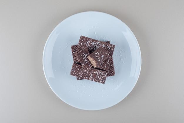 Bolachas cobertas de chocolate empilhadas em uma bandeja branca sobre fundo de mármore.