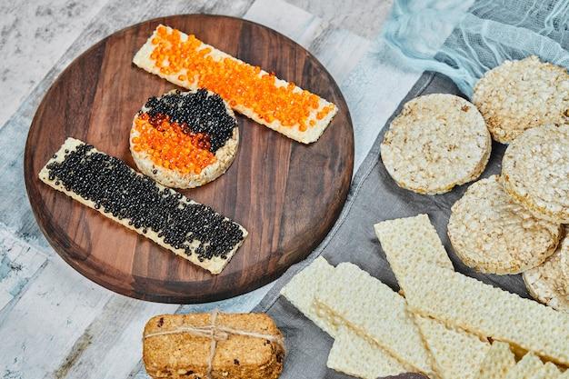 Bolachas com caviar vermelho e preto no topo.