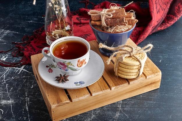 Bolachas com uma xícara de chá e frutas cítricas.