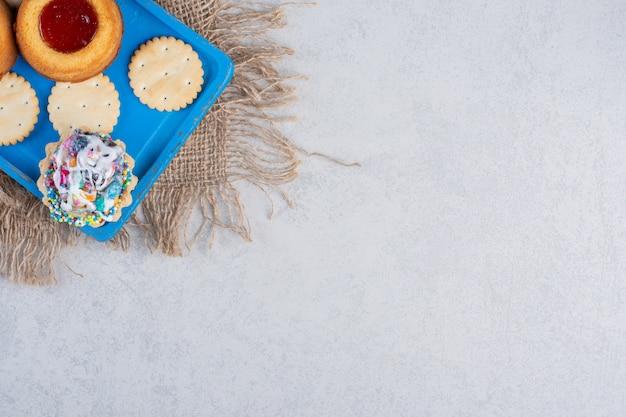 Bolachas, cupcakes e bolos recheados de geleia em uma travessa azul na mesa de mármore.