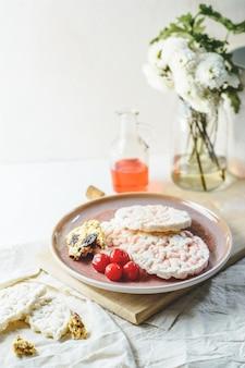 Bolachas de arroz com xarope de cereja e barra de cereais, e algumas cerejas, flores.