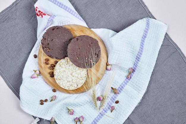 Bolachas de arroz e chocolate em uma placa de madeira com uma toalha de mesa.