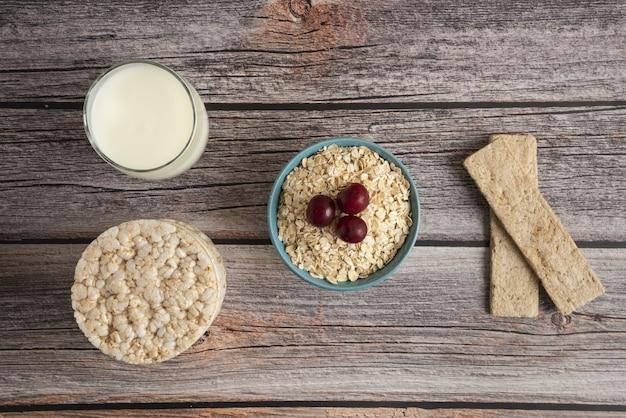 Bolachas de aveia, grãos com frutas vermelhas e um copo de leite na mesa, vista de cima