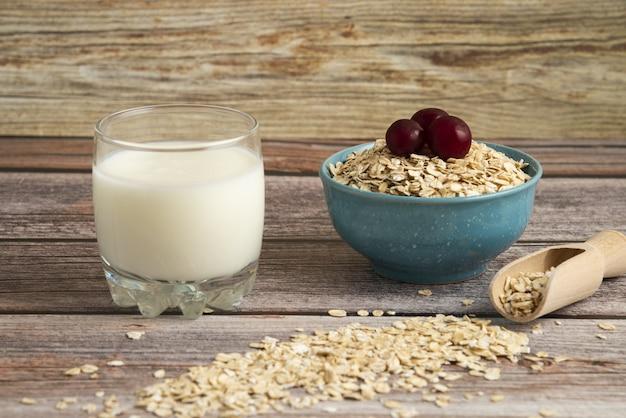 Bolachas de aveia, grãos com frutas vermelhas e um copo de leite na mesa