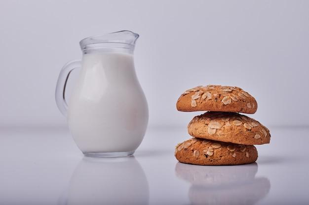 Bolachas de aveia servidas com um pote de leite em cinza.