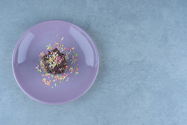 Bolachas de chocolate com polvilhe na placa roxa.