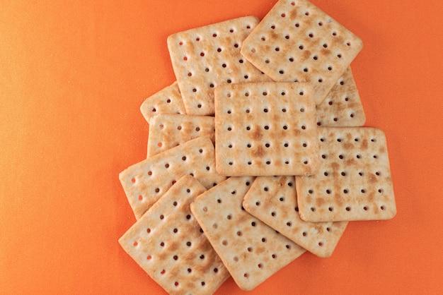 Bolachas de sal no fundo laranja Foto gratuita