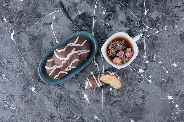 Bolachas de shortbread revestidas de chocolate branco e amargo com uma xícara de chá.