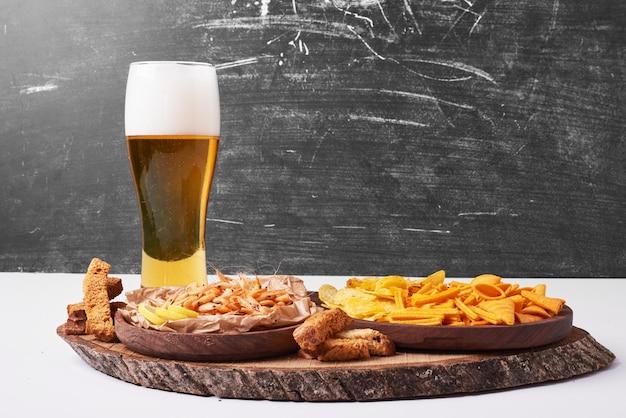 Bolachas e batatas fritas com um copo de cerveja em branco.