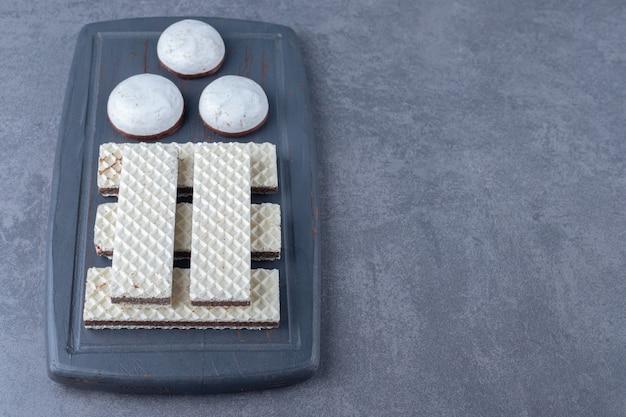 Bolachas e bolos em uma bandeja de madeira na mesa de mármore.