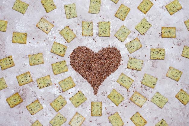 Bolachas em forma de coração de sementes de linho com azeite, sementes de linho e verdes, vista superior