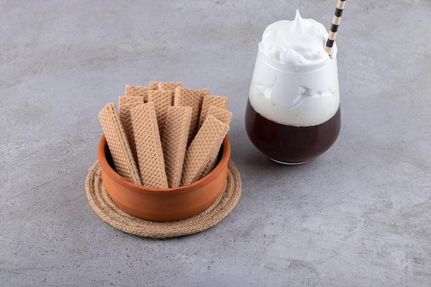 Bolachas em uma tigela com milk-shake em fundo cinza.
