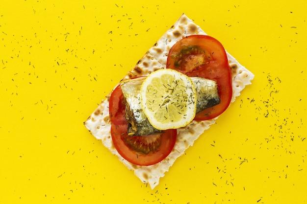 Bolachas salgadas com sardinha, tomate e limão por cima