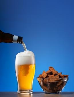 Bolachas salgadas de centeio e cerveja derramando em vidro