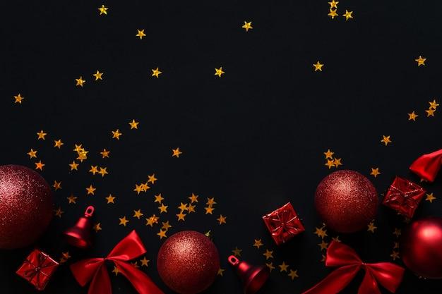 Bolas, arcos e sinos vermelhos em um fundo preto. layout de decorações de natal.