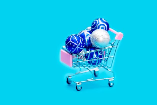 Bolas azuis de natal estão empilhadas em um pequeno carrinho de compras.
