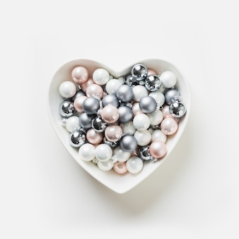 Bolas brancas, cor-de-rosa, cinzentas coloridas decorativas do natal na forma da placa do coração no conceito branco do xmas do fundo. isolado.