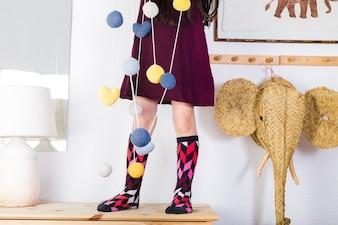 Bolas coloridas e corações pendurado na corda na frente da garota de pé sobre a mesa