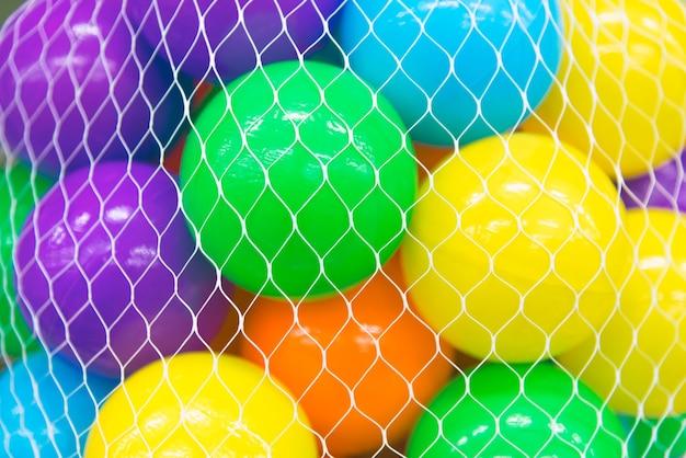 Bolas coloridas em uma capa de rede branca ou bolsa de rede.