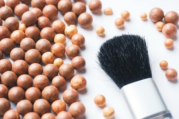 Bolas coram e uma escova cosmética. foco seletivo.