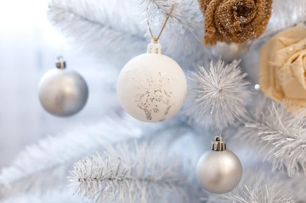 Bolas das decorações do white christmas que penduram em uma árvore de natal branco decorativa.