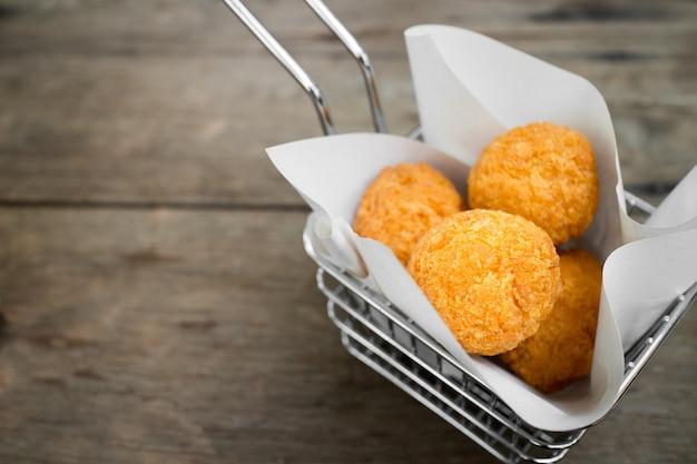 Bolas de arancini bolas de croquete de batata bolas de queijo bolas de arroz frito em fundo de madeira marrom
