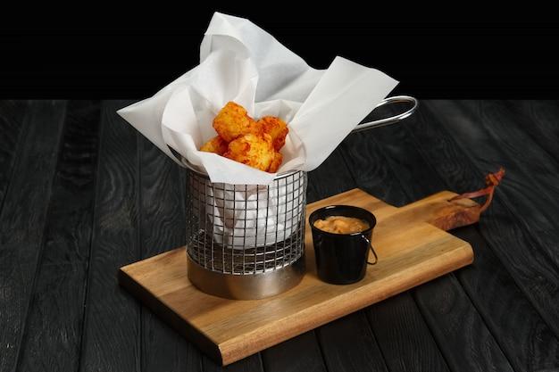 Bolas de batata frita em cesta de metal na placa de madeira