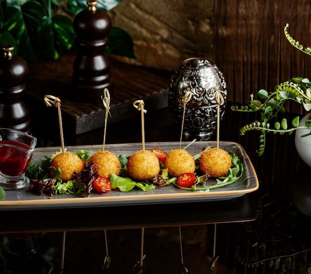 Bolas de batata servidas com legumes frescos como acompanhamento