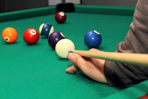 Bolas de bilhar na mesa verde e mão com taco de bilhar