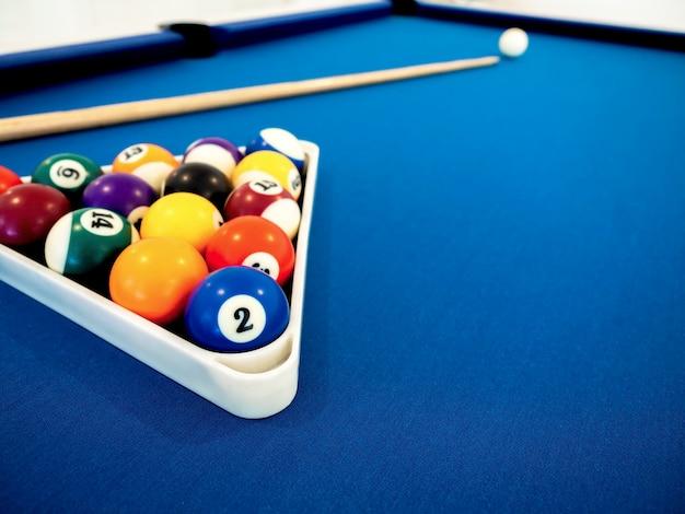 Bolas de bilhar no triângulo branco e taco na mesa azul com espaço de cópia. conceito de esporte de bilhar. jogo de bilhar.