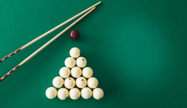Bolas de bilhar russo, taco, triângulo, giz sobre uma mesa.