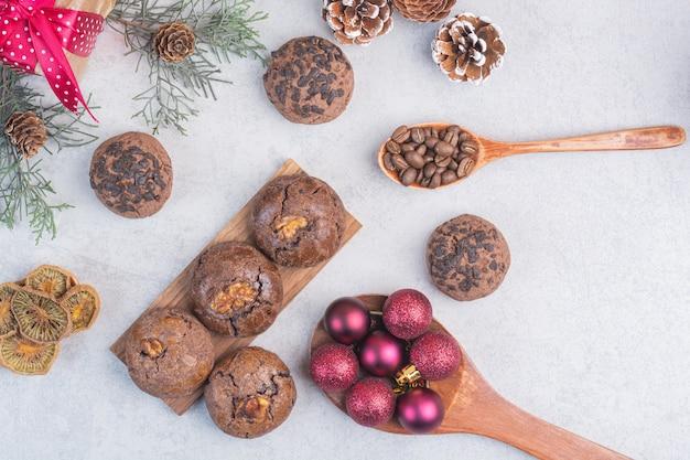 Bolas de biscoito de chocolate, colher, pinha, caixa de presente, grãos de café, no mármore.