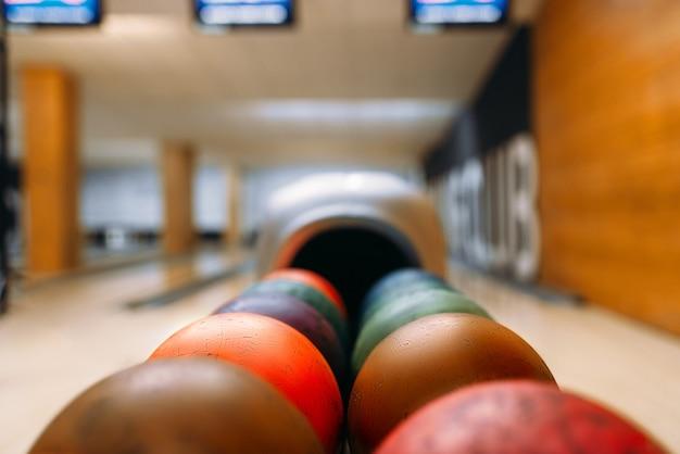 Bolas de boliche coloridas no alimentador, conceito de jogo de boliche