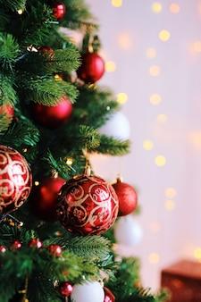 Bolas de brinquedo vermelho brilhante na árvore de natal com luzes