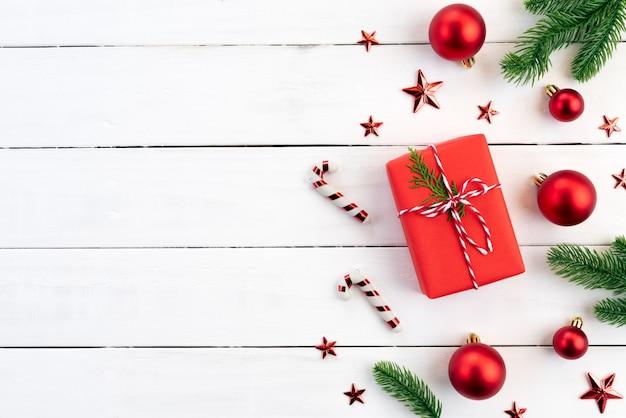 Bolas de caixa de presente de natal vermelha com ramos de abeto, pinhas, bagas vermelhas em backg de madeira