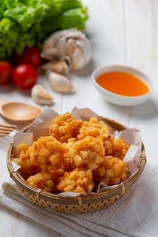 Bolas de camarão cobertas com à milanesa frita na superfície de madeira branca.