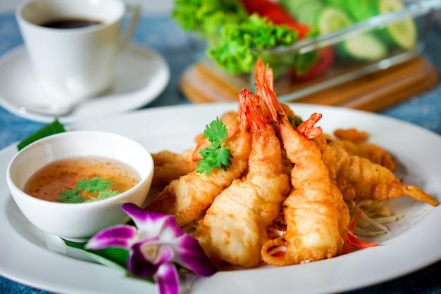 Bolas de camarão frito na mesa azul com molho doce e copo de café branco e vegetais