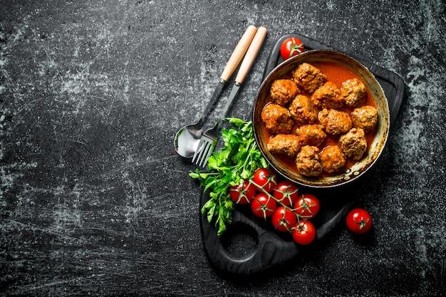 Bolas de carne em uma panela em uma placa de corte com tomate e salsa. em fundo rústico