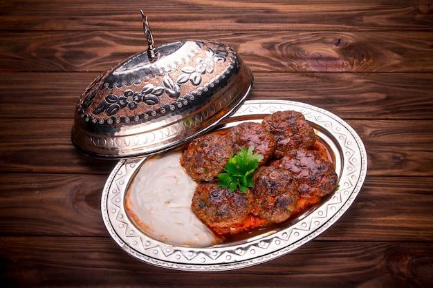 Bolas de carne kebab de carne com molho na mesa de madeira