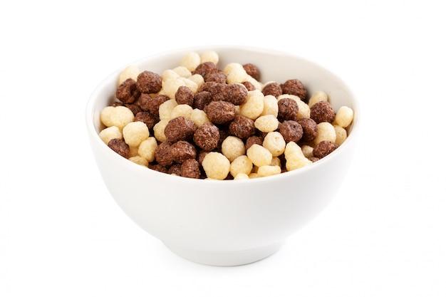 Bolas de cereais para o café da manhã em uma tigela isolado no branco