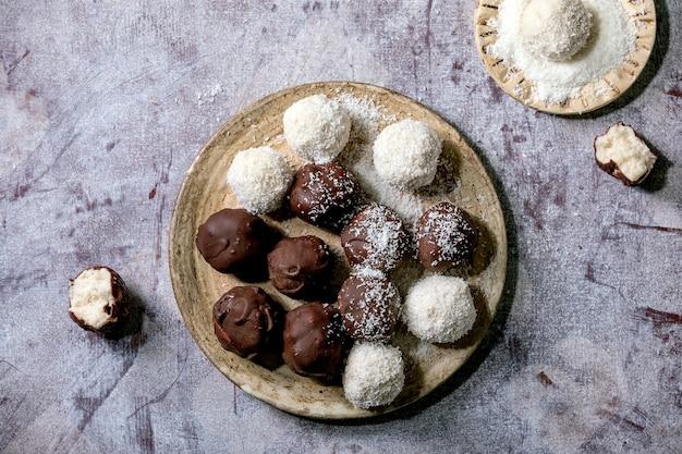 Bolas de chocolate de coco caseiro vegan cru com flocos de coco em placa de cerâmica sobre fundo branco de madeira