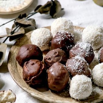 Bolas de chocolate de coco caseiro vegan cru com flocos de coco em placa de cerâmica sobre fundo branco têxtil com galhos de eucalipto. imagem quadrada