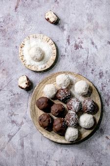 Bolas de chocolate de coco caseiro vegan cru com flocos de coco na placa de cerâmica sobre a superfície de madeira branca. camada plana, espaço de cópia