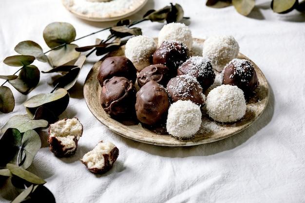 Bolas de chocolate de coco caseiro vegan cru com flocos de coco na placa de cerâmica sobre a superfície têxtil branca com galhos de eucalipto. Foto Premium