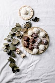 Bolas de chocolate de coco caseiro vegan cru inteiras e quebradas com flocos de coco na placa de cerâmica sobre a superfície de tecido branco com galhos de eucalipto. postura plana, espaço